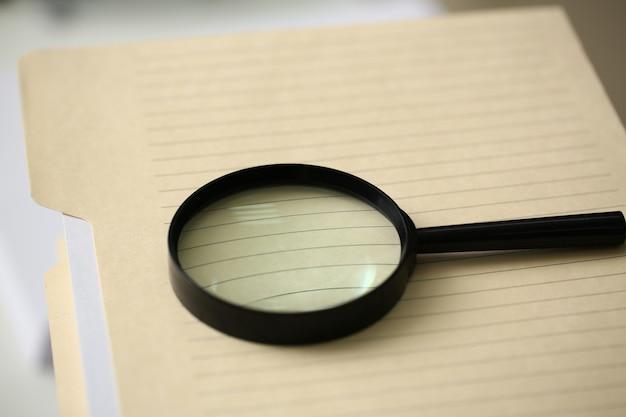 La lente de lectura negra está en la página de error de la carpeta de seguro de propagación amarilla que no se encuentra.