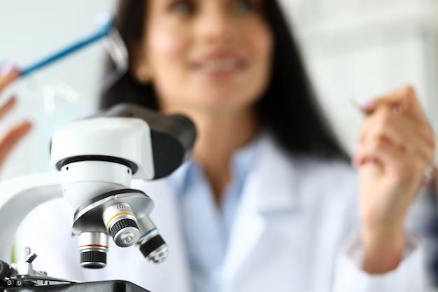 Lente de microscopio científico con analista femenina en segundo plano.