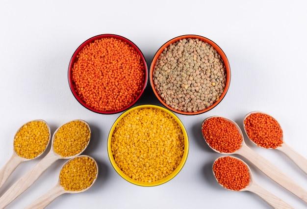 Lentejas amarillas y rojas en cucharas de madera y cuencos de diferentes colores.