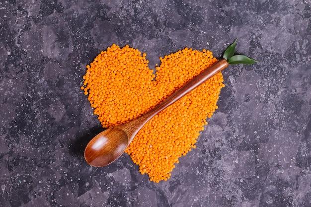 Lentejas de naranja cruda para una nutrición y salud adecuadas en forma de corazón con una cuchara de madera y hojas sobre un fondo gris