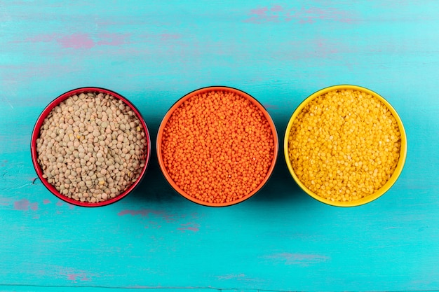 Lentejas rojas, amarillas y verdes en un recipiente rojo y amarillo plano