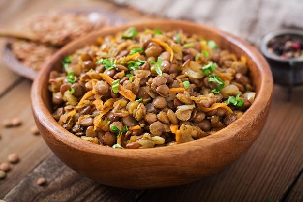 Lentejas con zanahoria y cebolla en un tazón de madera