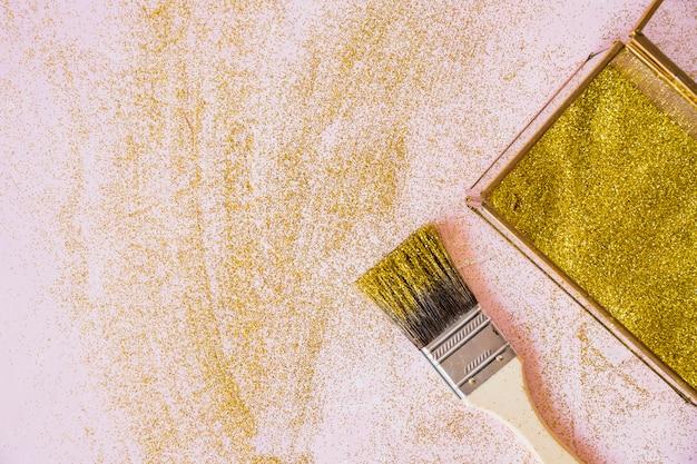 Lentejuelas amarillas en caja con pincel