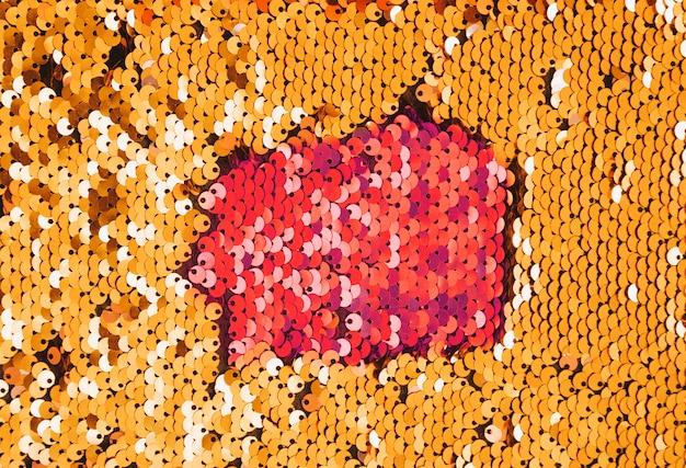 Lentejuelas doradas cosidas sobre la tela en estilo disco.