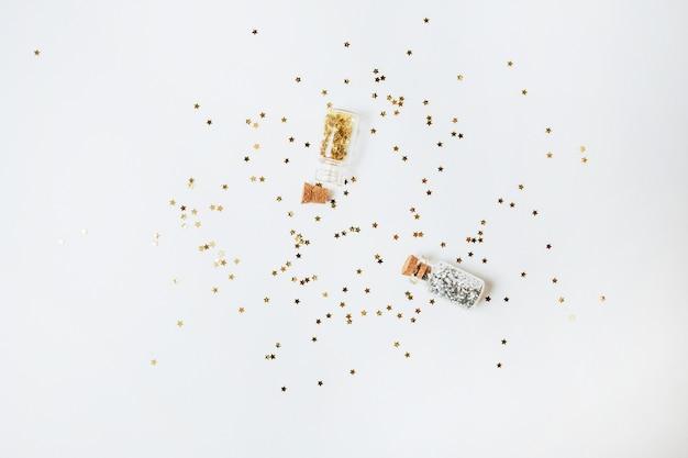 Lentejuelas de oro y plata se esparcen de botellas