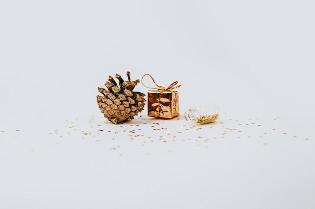 Las lentejuelas de oro y plata están esparcidas desde botellas, regalo y cono de abeto y un regalo sobre un fondo blanco.