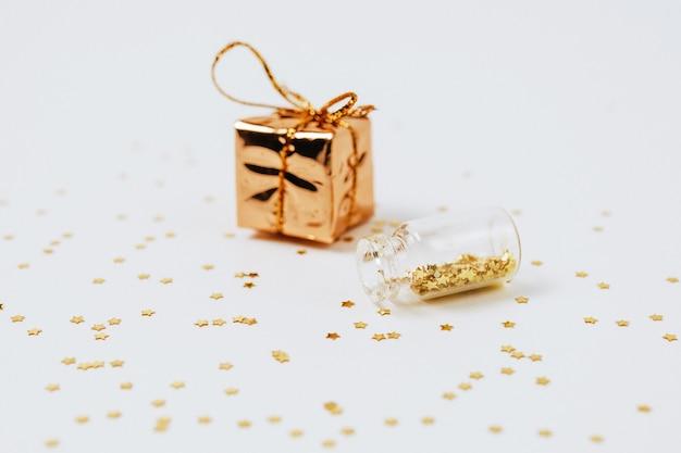 Las lentejuelas de oro y plata están esparcidas desde botellas y un regalo sobre un fondo blanco.