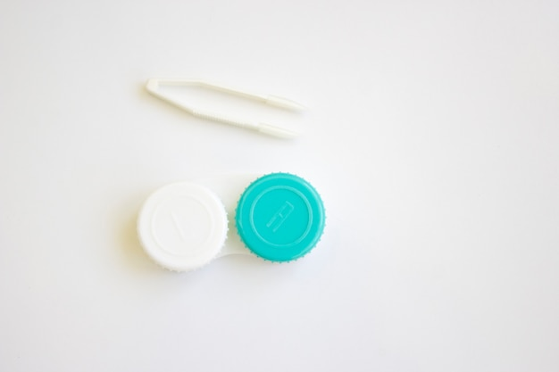 Lentes de contacto en un recipiente y pinzas para lentes