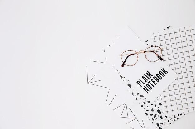 Lentes en cuaderno liso y páginas sobre fondo blanco.