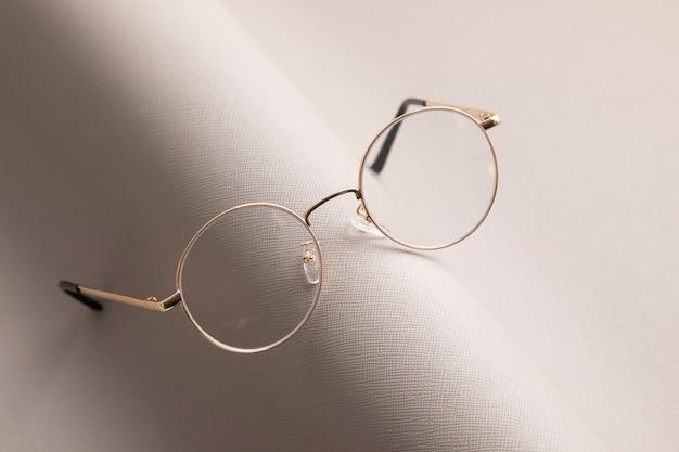Lentes con estilo sobre pared gris. tienda de óptica, selección de gafas, examen de la vista, examen de la vista en el óptico, concepto de accesorios de moda