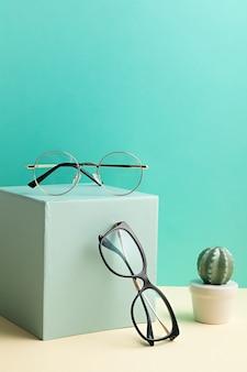 Lentes con estilo sobre pared pastel. tienda de óptica, selección de gafas, examen ocular, examen de la vista en el óptico, concepto de accesorios de moda. vista frontal