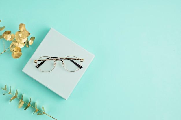 Lentes con estilo sobre pared pastel. tienda de óptica, selección de gafas, examen ocular, examen de la vista en el óptico, concepto de accesorios de moda. vista superior, endecha plana