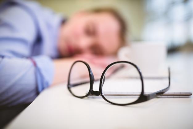 Lentes en la mesa contra empresaria soñolienta