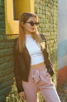 Lentes que llevan de moda hermosos de la mujer joven que se inclinan contra la pared de ladrillo verde