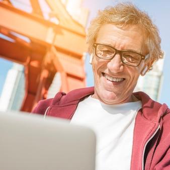 Lentes que llevan sonrientes del hombre mayor usando el ordenador portátil
