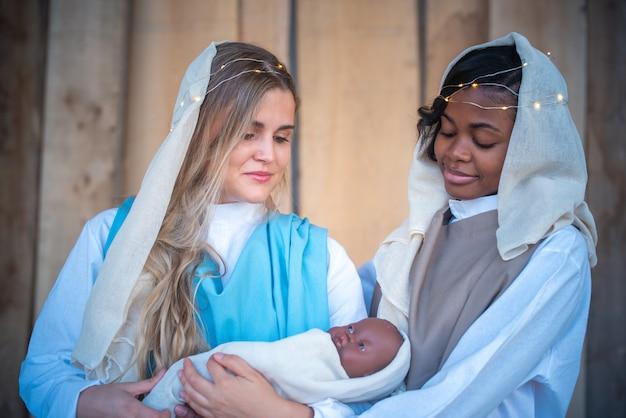 Lesbiana mujer caucásica y afro que representa a la virgen maría mientras sostiene a un niño jesús negro en una cuna