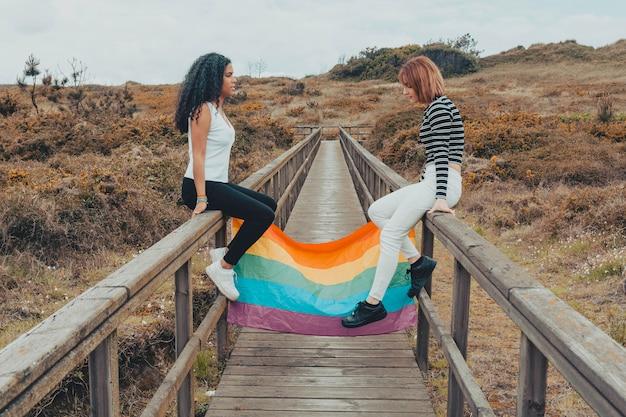 Lesbianas sosteniendo la bandera del arco iris
