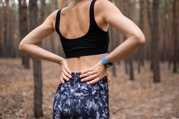 Lesión deportiva mujer de dolor de espalda baja que sostiene el cuerpo tocando los músculos de la cintura dolorosos que muestran reloj inteligente en la muñeca.
