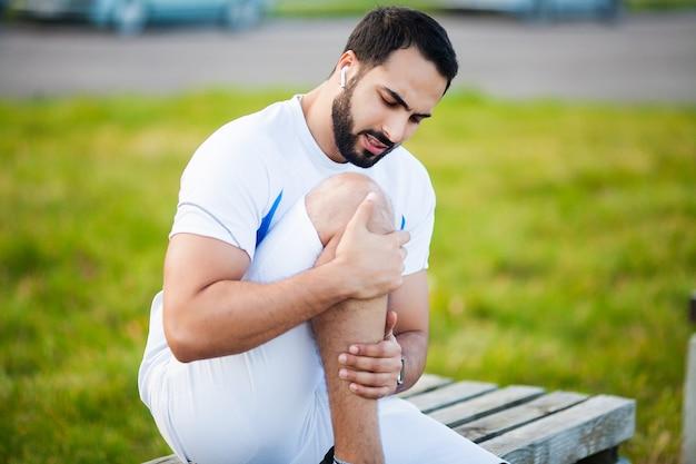 Lesión en una pierna. atleta masculino sufriendo de dolor en la pierna mientras hace ejercicio al aire libre