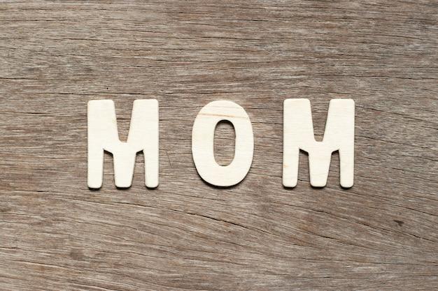 Letra del alfabeto en la palabra mamá en la madera