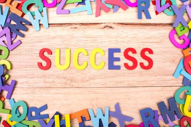 Letra de madera colorida del alfabeto y la palabra éxito aislado sobre fondo de madera