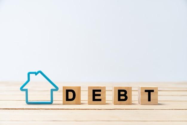Letra de madera deuda con modelo de casa azul sobre blanco.