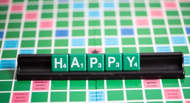 La letra scrabble verde está deletreando la palabra feliz en el estante