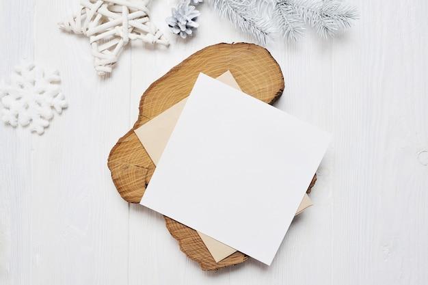 Letra de tarjeta de felicitación de navidad de maqueta en envolvente con árbol blanco