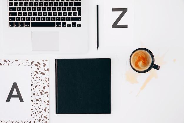 Letra a y z; lápiz; diario; ordenador portátil y taza de café derramado sobre fondo blanco