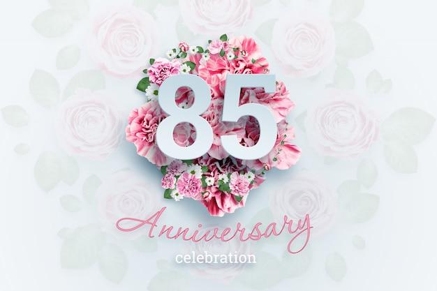 Letras 85 números y texto de celebración de aniversario en flores rosadas.
