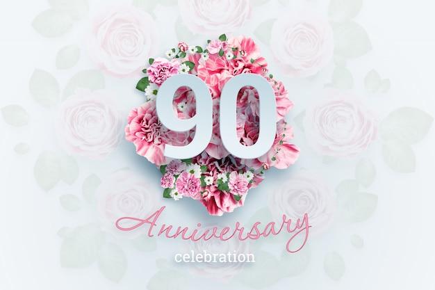 Letras 90 números y texto de celebración de aniversario en flores rosadas.