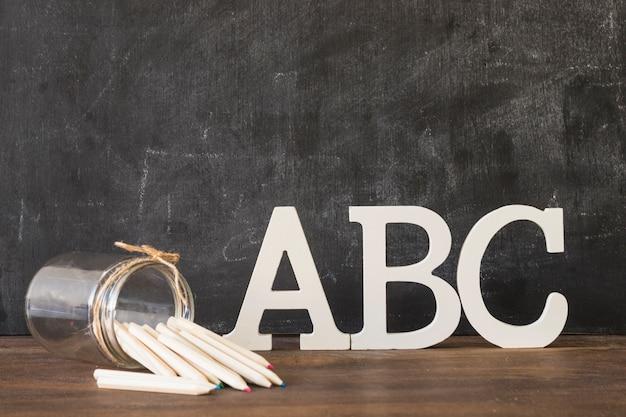 Letras del alfabeto con plumas en la mesa