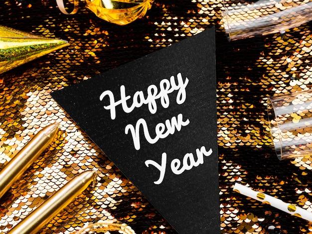 Letras de año nuevo sobre fondo de lentejuelas doradas