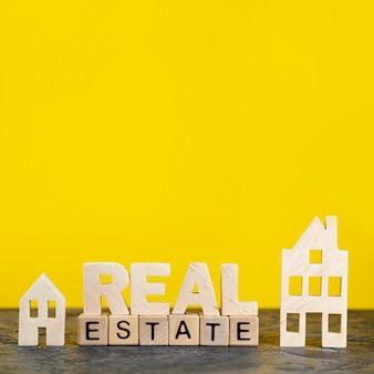 Letras de bienes raíces de vista frontal sobre fondo amarillo