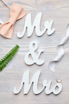 Letras blancas sr. y sra. con cinta, rama, anillo, mariposa sobre un fondo de madera. vista superior.