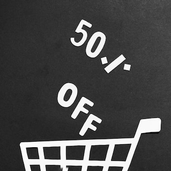Letras de papel con oferta de venta y carrito de compras