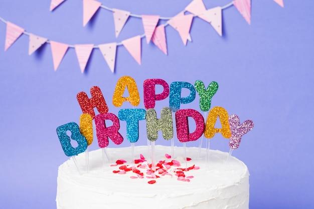Letras de feliz cumpleaños en delicioso pastel