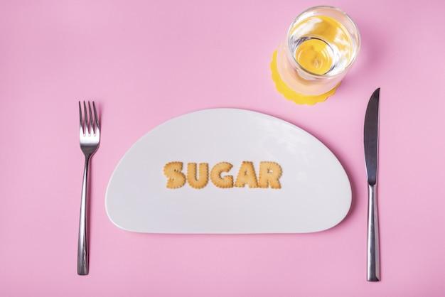 Letras de galleta en plato de porcelana, azúcar