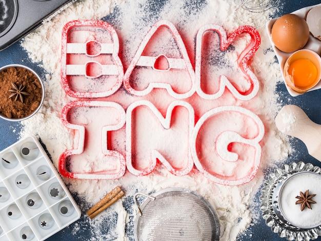 Letras de harina de ortografía hornear con herramientas e ingredientes de alimentos dulces azúcar, huevos, cacao, canela.