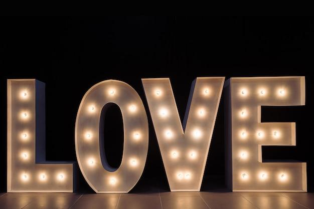 Letras iluminadas con bombillas que forman la palabra amor sobre un fondo negro