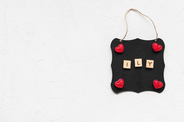 Letras ily y corazones de gelatina en un tablero