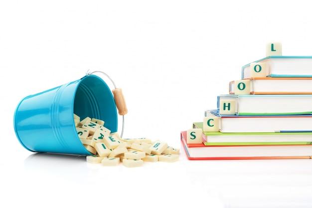 Las letras inglesas se derraman del cubo y la palabra educación en los libros.