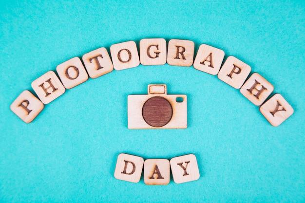 Letras de madera, inscripción en un fondo azul brillante. dia internacional de la fotografia