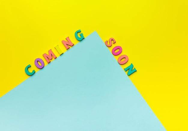 Letras de madera de juguete que explican próximamente con un fondo amarillo