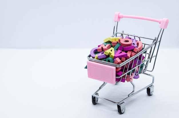 Letras de madera multicolores en un carro de supermercado de metal sobre un fondo blanco. concepto: regreso a clases, alfabetización, lectura, aprendizaje de idiomas. espacio para texto