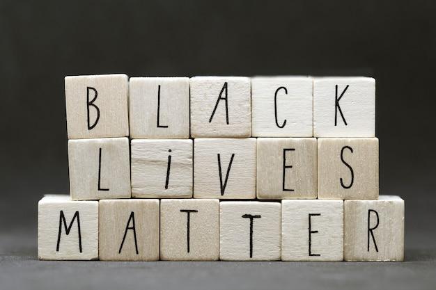 Letras de madera que forman las palabras 'las vidas negras importan' sobre fondo negro oscuro concepto de justicia o blm