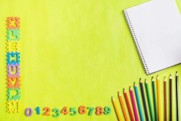 Letras y números cerca de lápices y cuaderno