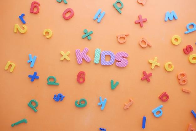 Letras de plástico de colores en la vista superior de la superficie naranja