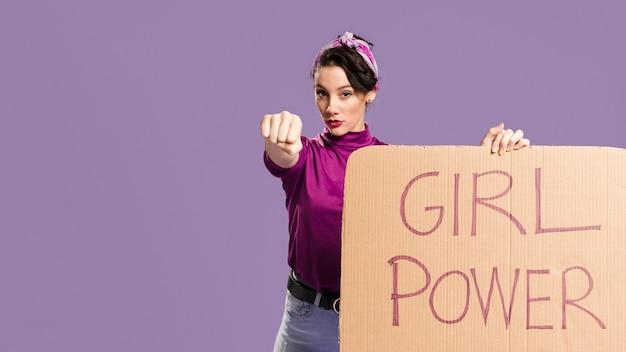 Letras de poder de niña en cartón y mujer mostrando su puño