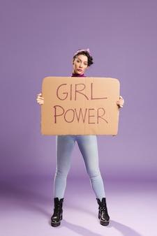 Letras de poder de niña en cartón y mujer de pie